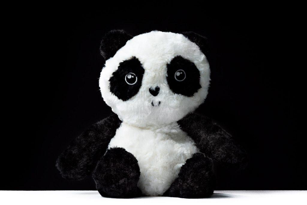 Panda bear plush toy on a black background