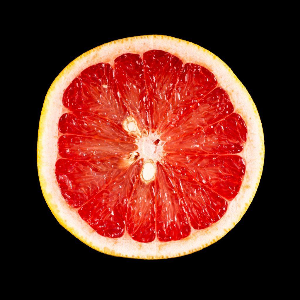 red grapefruit on black background